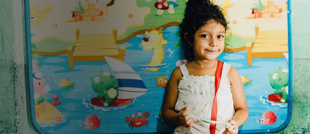 A young girl holding a toothbrush