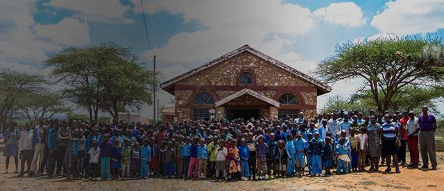 A group of adults and children standing in front of a church in Kenya