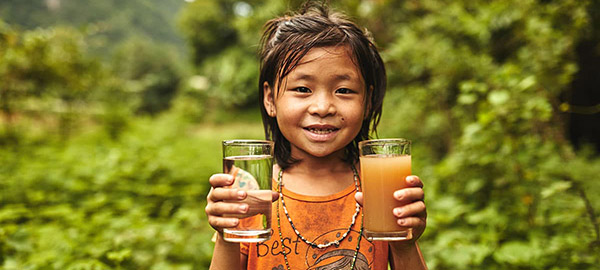 A girl holding a glass of dirty water and a glass of clean water