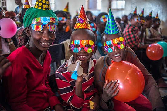children wearing party hats and party masks