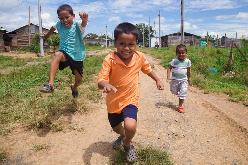 Three brothers from northern Colombia smile as they run down a dirt road