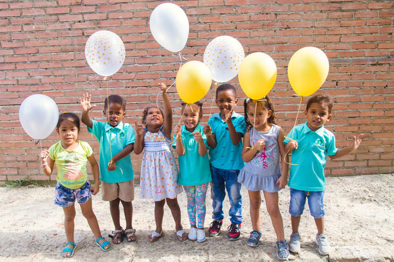 A group of children celebrate New Year's Eve with colorful balloons