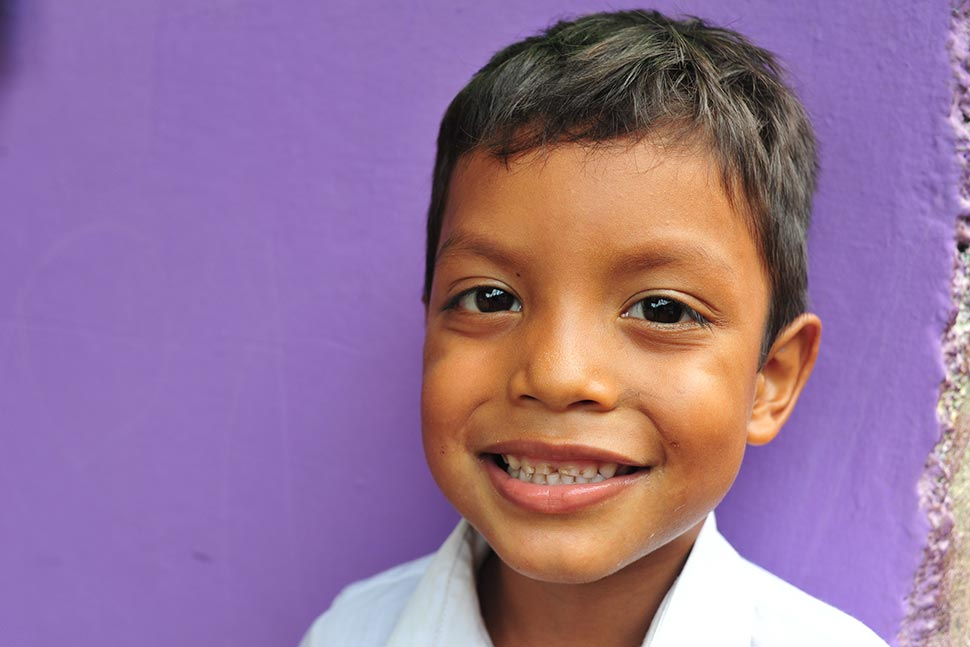 A smiling young boy stands in front of a purple wall