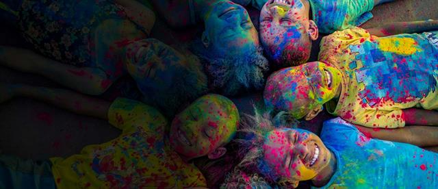 Children covered in colorful powder lie on their backs in a circle with their heads touching