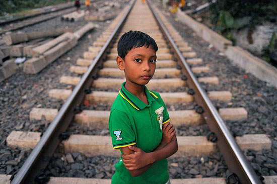 A young Indian boy stands in the middle of some train tracks.