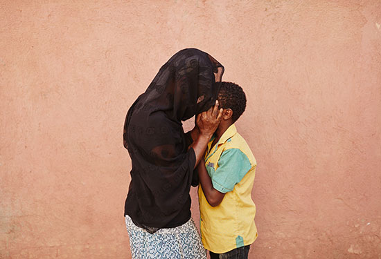 A boy and a woman wearing a black head press their foreheads against one another