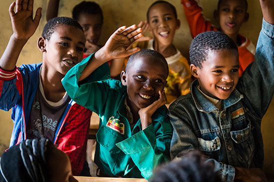 A group of Ethiopian boys raise their hands in class.