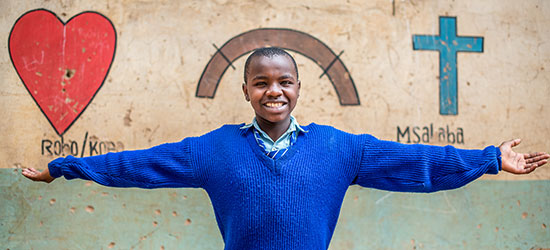 A Kenyan girl in a blue sweater stretches her arms out to the side.