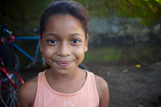 A young Nicaraguan girl smiling with pursed lips.