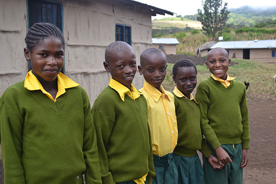 A group of Tanzanian children stand outside together.