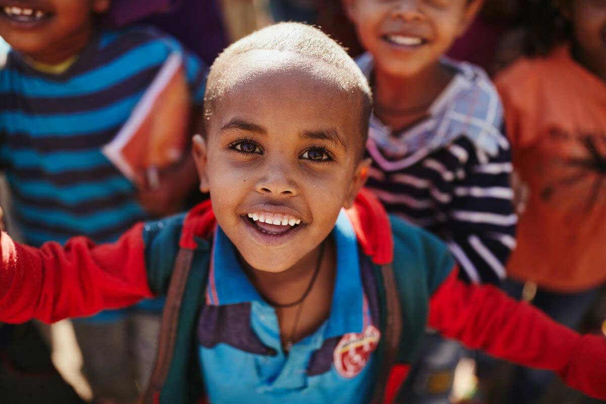 An Ethiopian boy stretching our his arms and smiling
