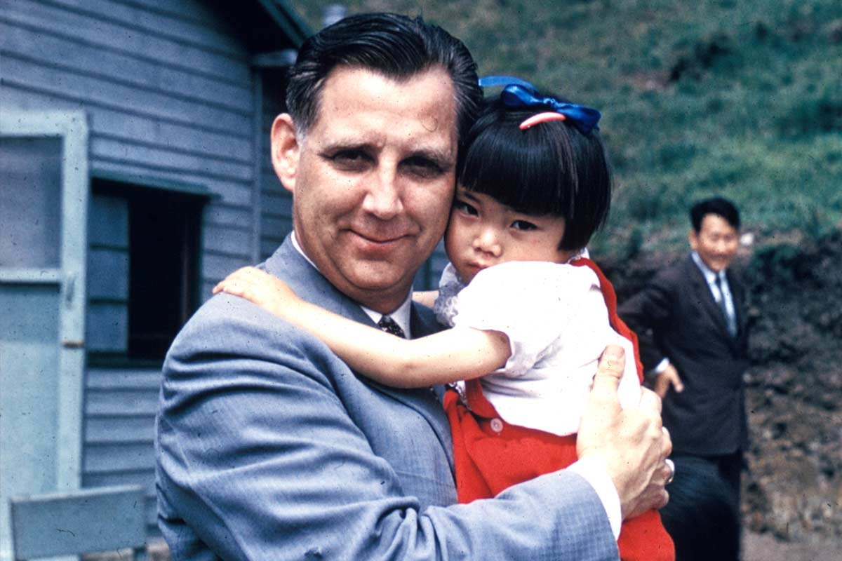 Reverend Everett Swanson holding a young girl in South Korea