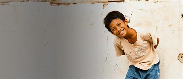 A boy in a white shirt bends at the waist in front of a white wall