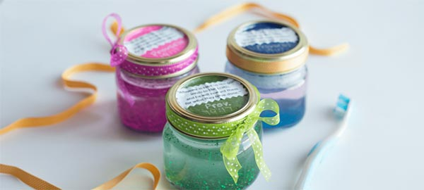 Three small mason jars with ribbon around the lids and different color homemade glitter toothpaste in them