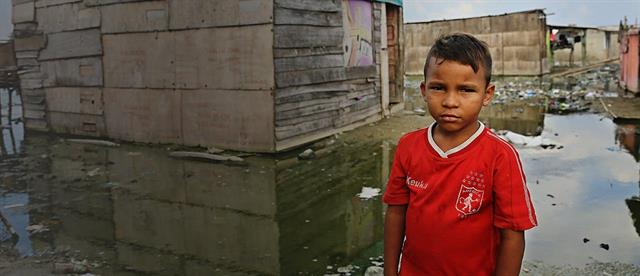 A solemn looking boy in a red shirt stands in front of a flooded house