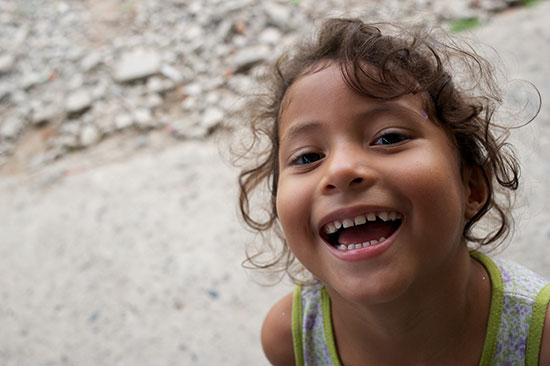 A young curly-haired Ecuadorian girl laughing