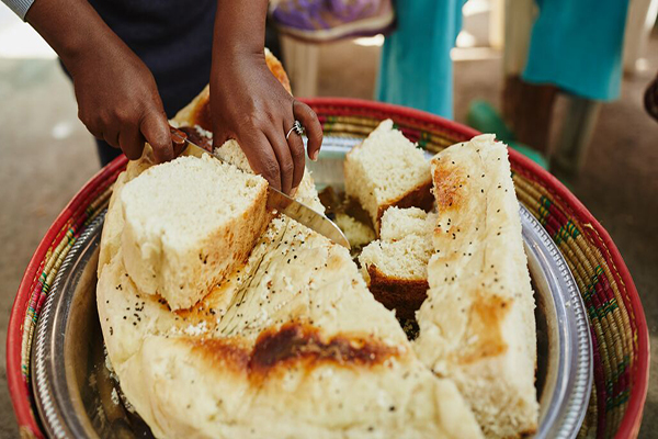 An Ethiopian woman uses a knife to cut into a large loaf of dabo.