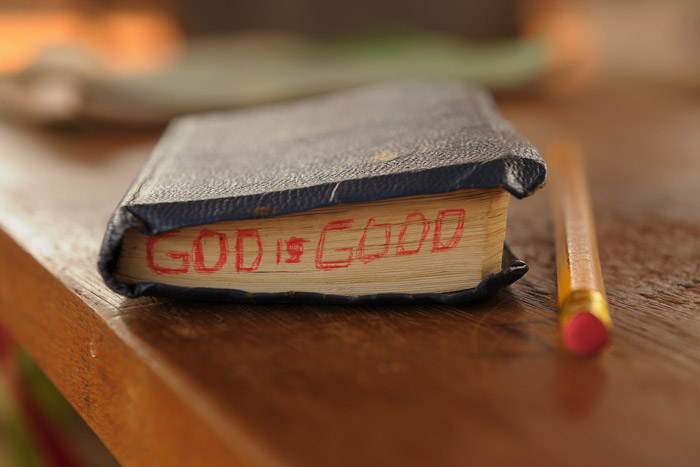 "Close up of a bible with the words ""God is good"" on it"