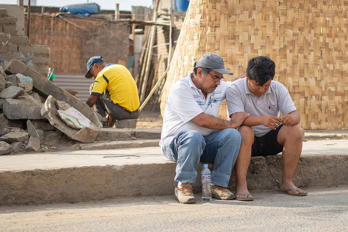 A disaster relief volunteer sits and prays with a young man affected by the event
