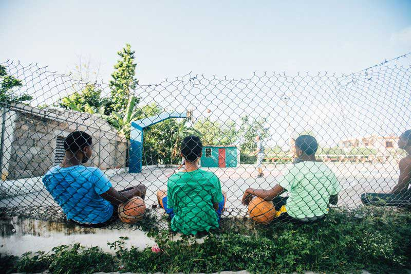 Four boys take a break from playing and sit against a fence with their basketballs