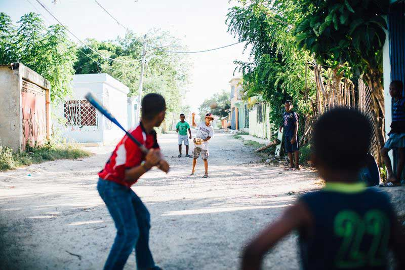 A group of children play baseball in the street