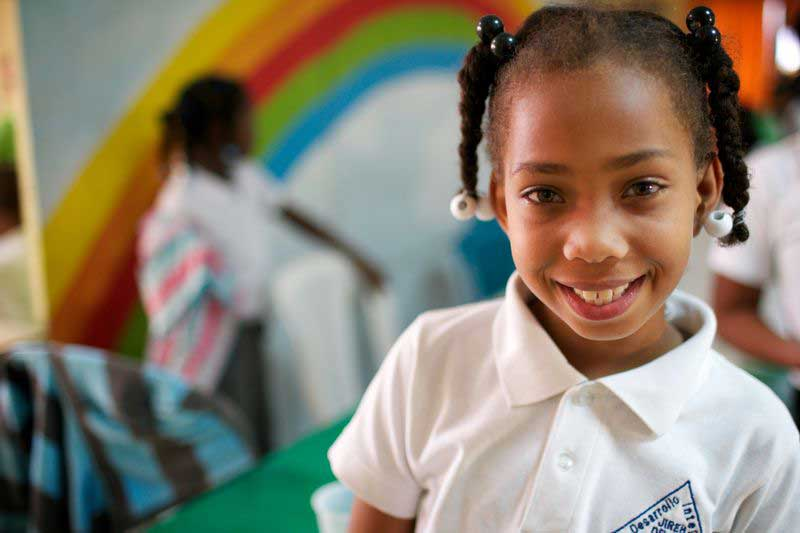 A girl smiles in front of a rainbow-painted wall in her classroom