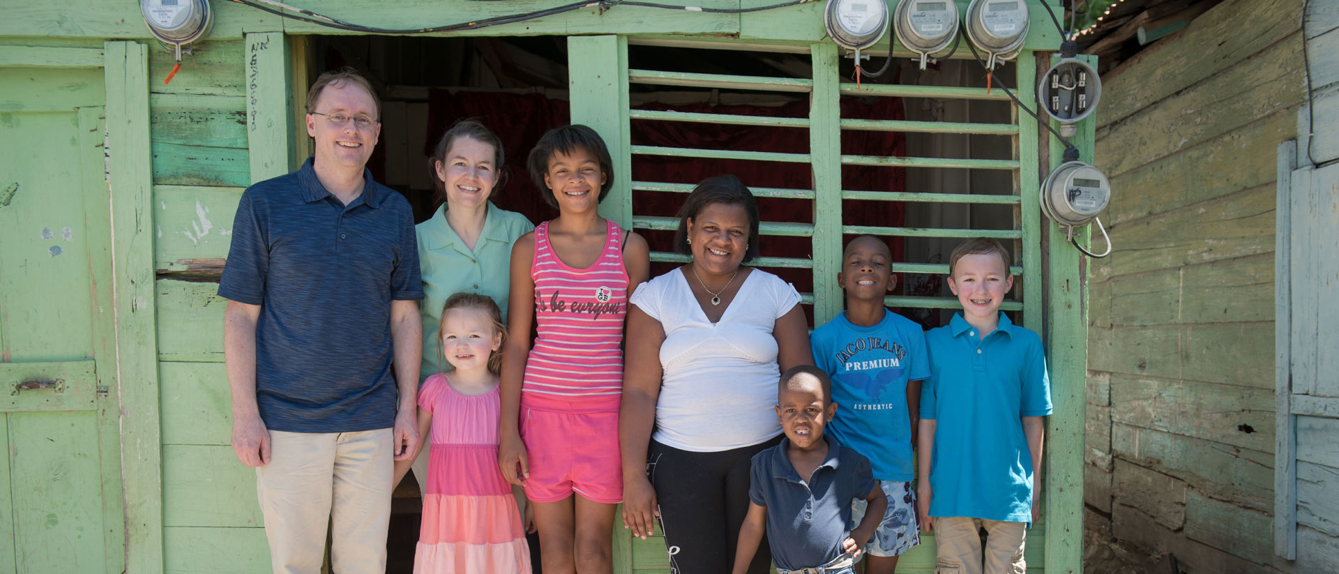 Alexander and Ian's family together outside home in Domincan Republic