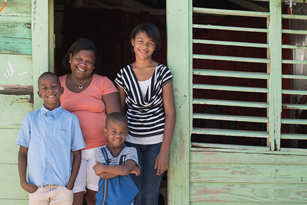Dominican family stands outside their home in Domincan Republic.