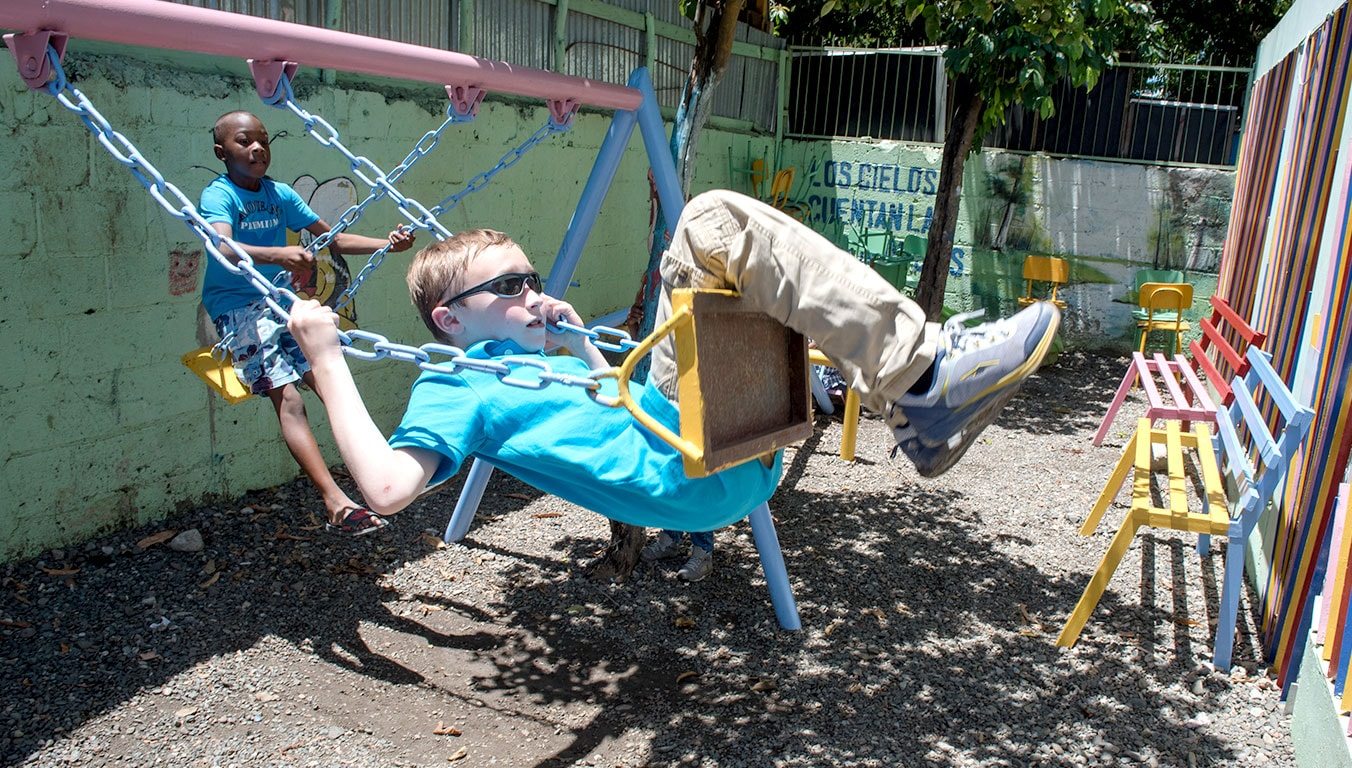 Alexander and Ian swing together outside