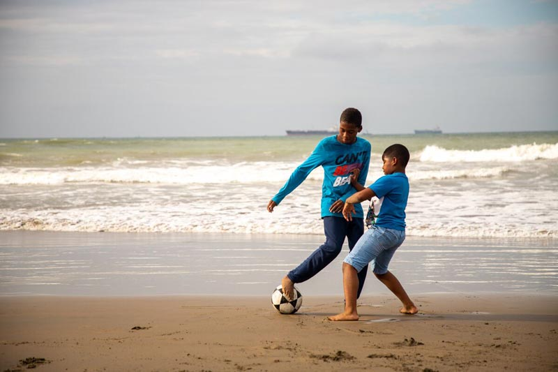 Boys play soccer on the beach