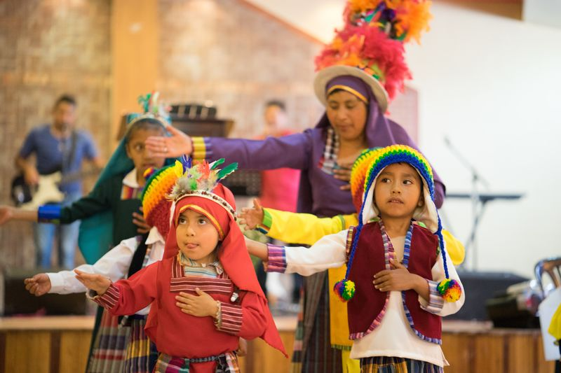 Children wear traditional Ecuadorian clothes as they dance on a festive occasion