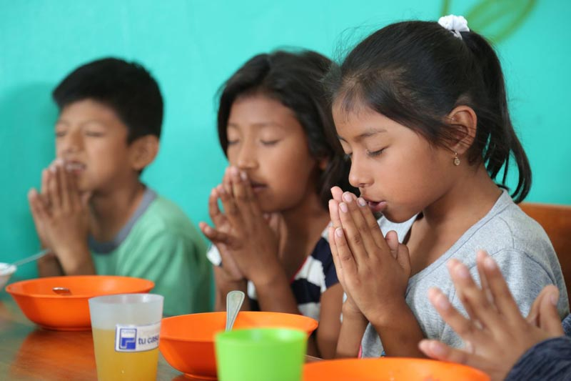 Children pray before their meal