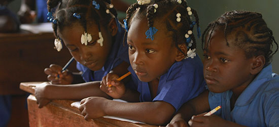 Three Haitian girls in blue school uniforms sit close together at a wooden desk.