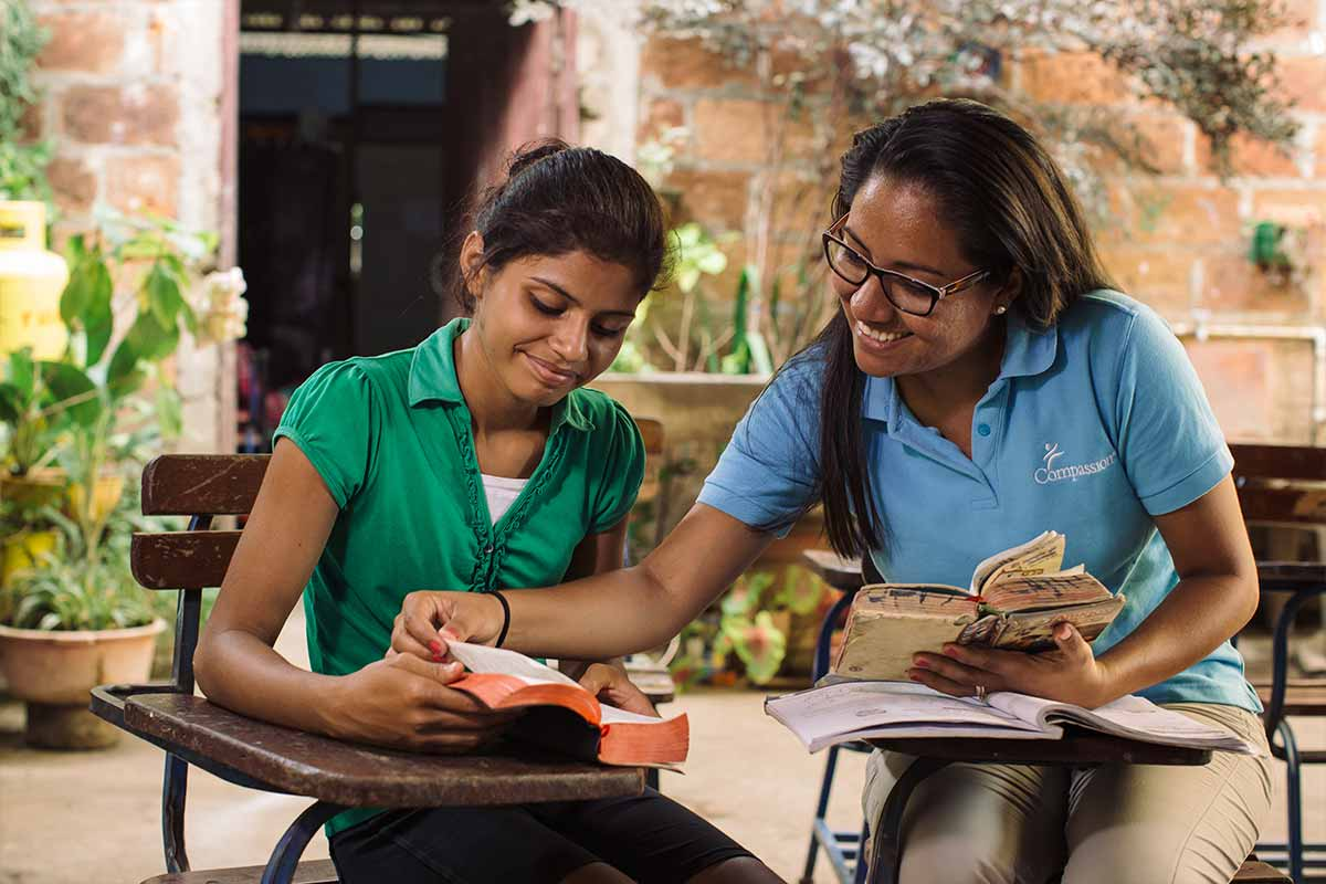 A young teenage girl sits with a Compassion worker and receives tutoring