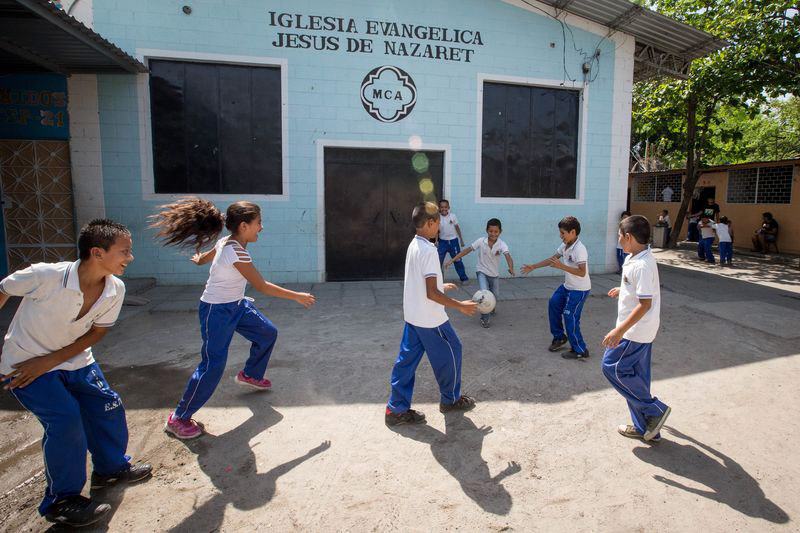 A group of children play soccer at their child development center