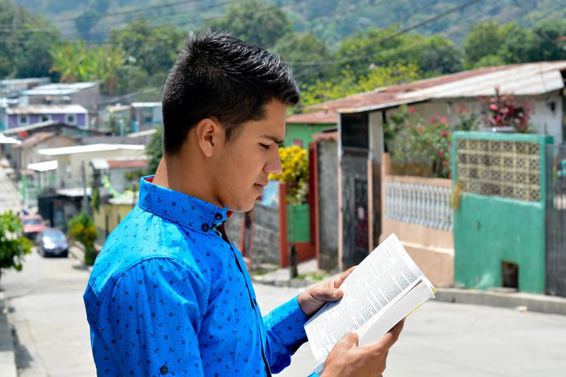 A teenager reads the Bible in his neighborhood