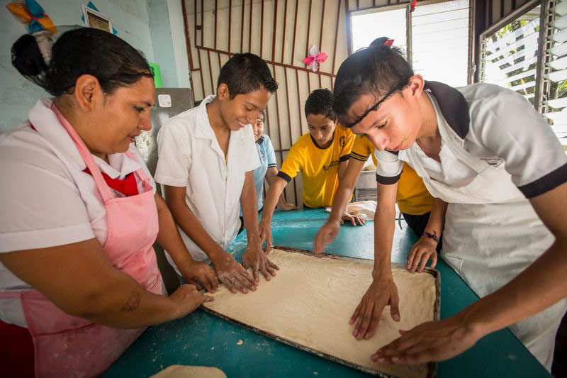 Young adults learn income-generating skills, like baking, at their child development center
