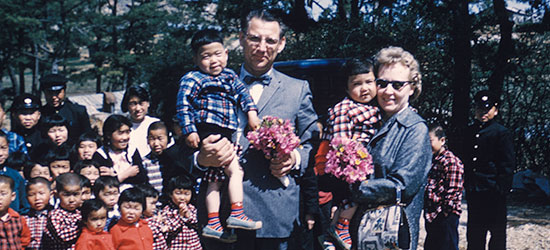 Everett and Miriam Swanson holding Korean War orphans.