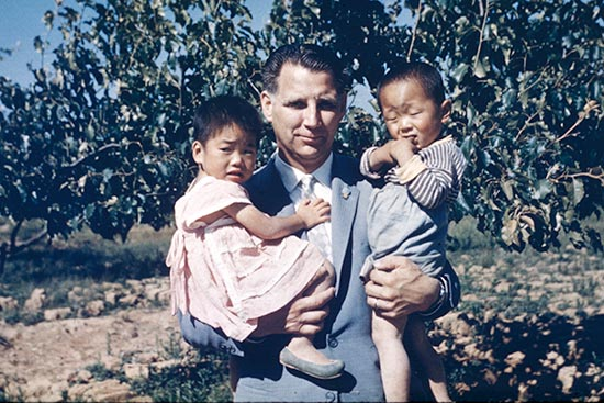 Rev. Everett Swanson holding two orphans in his arms.