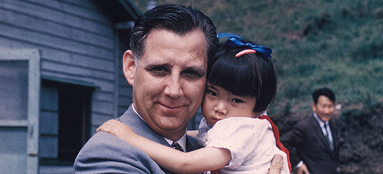 Rev. Everett Swanson holding a Korean War orphan.