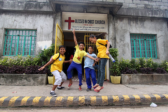 Four Filipino children jumping in the air in front of a church