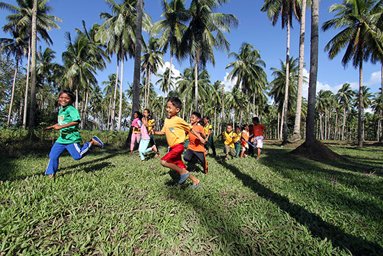 Several Filipino children running through palm trees