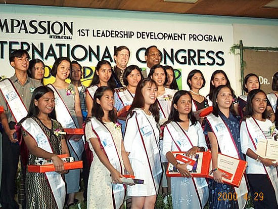 Filipino students stand together in a group smiling and wearing sashes.