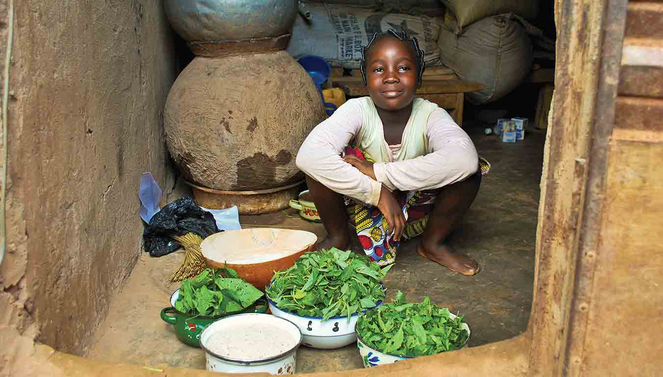 A young girl helps prepare ingredients for her family's meal
