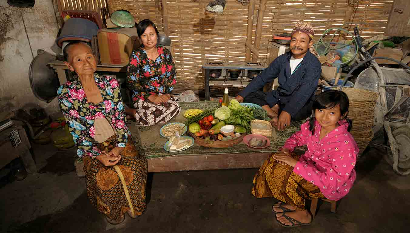 An Indonesian family sitting around a table and eating a meal