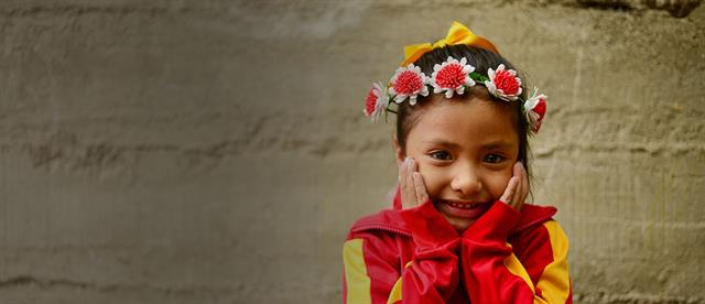 A smiling girl with a flower wreath headband places her hands on her cheeks
