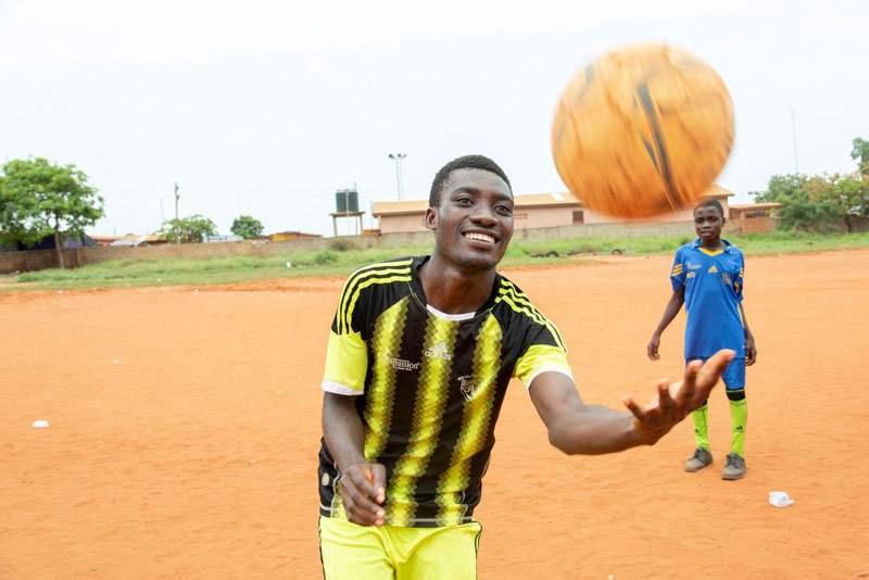 A young man plays with a soccer ball