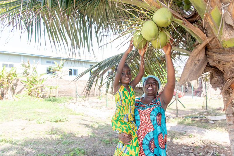 A girl and her mother smile as they reach for a coconut