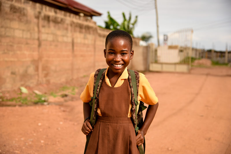 A smiling girl wears a backpack while walking down a dirt road