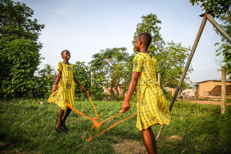 Two smiling girls play a game while holding a rope